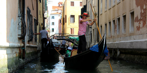Gondoliers guide travelers through Venice's maze of canals.